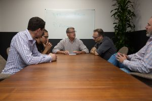 Men around conference table in group therapy